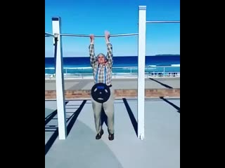 72 years old man doing pull up with 20 kg for 6 reps