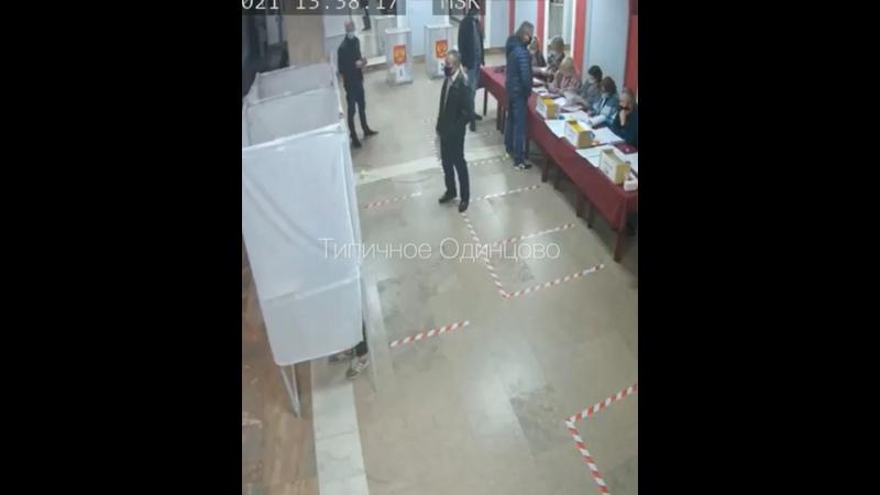 Председатель УИК 1976 в Одинцово с толстой пачкой бумаг прогуливается возле урны для голосования